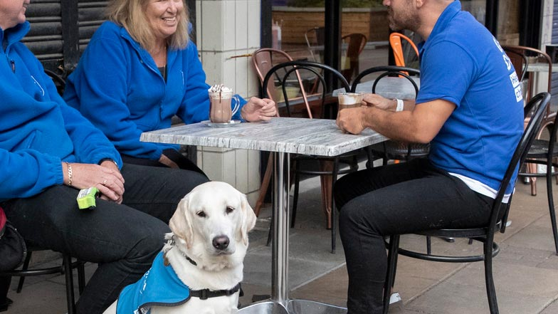 Eve sitting outside a cafe with Guide Dogs trainers