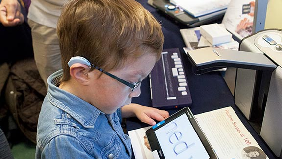 A boy using a screen magnifier on his tablet at a Guide Dogs event