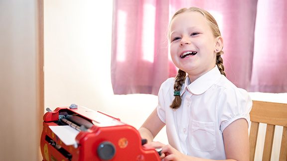 A young girl using a typewriter and smiling