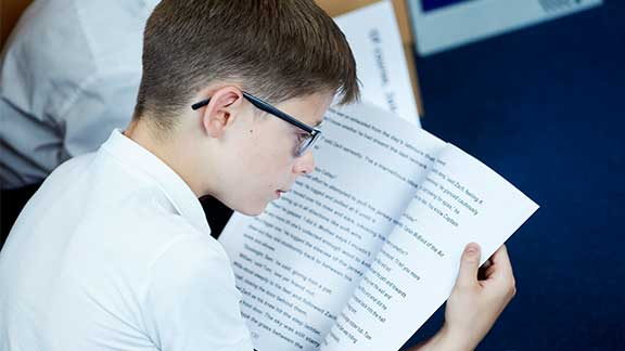 A boy reading one of Guide Dogs' CustomEyes books