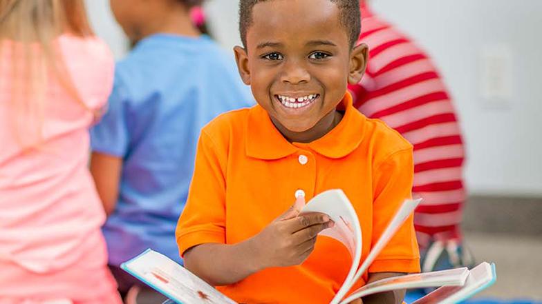A boy in a classroom enjoying reading a book