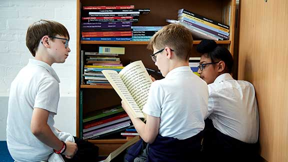 A group of school children looking at Guide Dogs' CustomEyes books