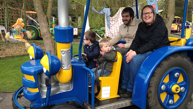 A family enjoying a theme park ride at a Guide Dogs event