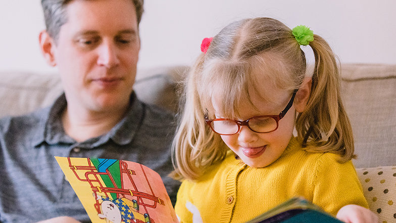 Young-girl-reading-book-with-dad