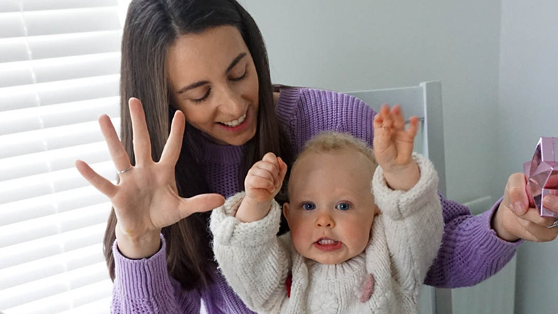 Mother and baby doing actions with their hands