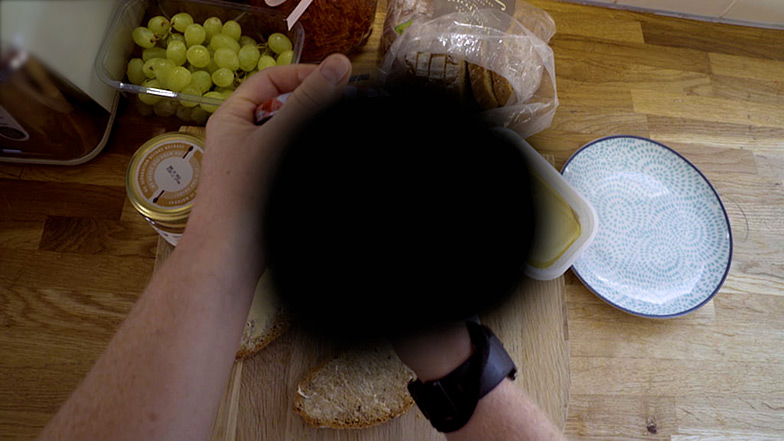 Hands holding a jar with a black spot in the centre of the image covering the jar