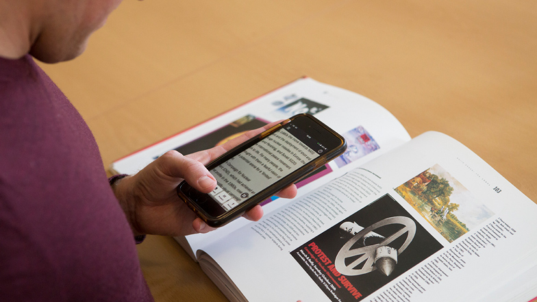 Guide Dogs service user using magnifying app on phone to read a textbook