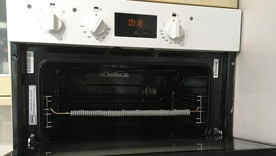 Image shows an oven cavity with an open door, the shelf has a grey shelf guard.