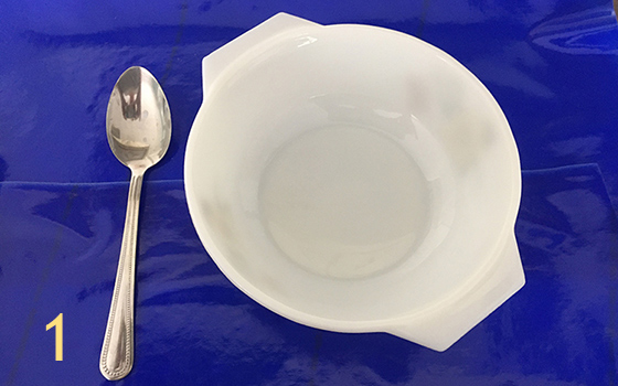 Image is labelled with the number one. Shows a white bowl and chrome spoon on a tray covered with a blue Dycem mat to highlight the contrast