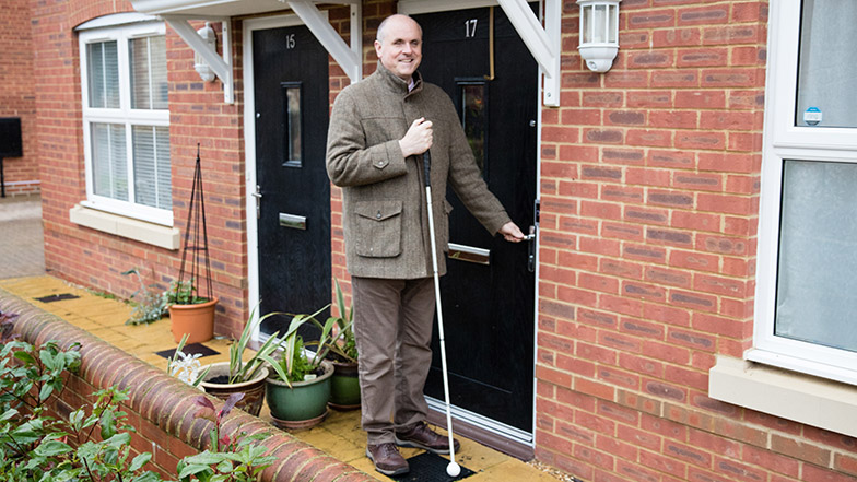 Guide Dogs' staff member John at the front door of his home with his Long Cane
