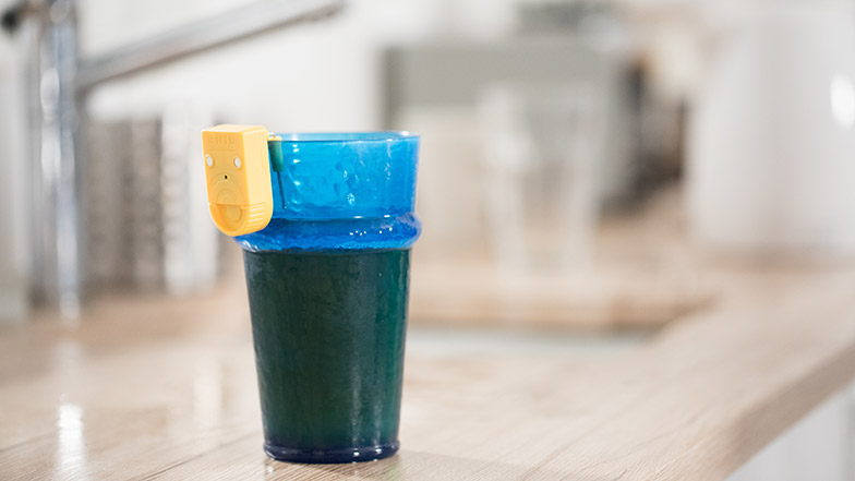 A picture of a blue glass with a liquid indicator attached to it.