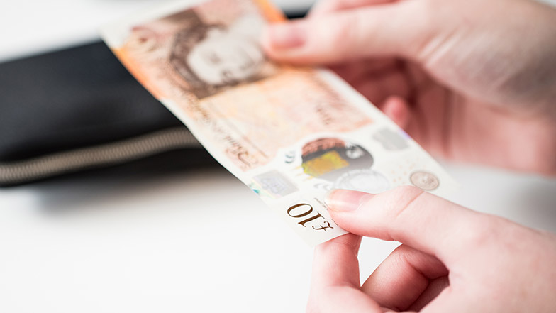 An image of a person holding a 10 pound banknote