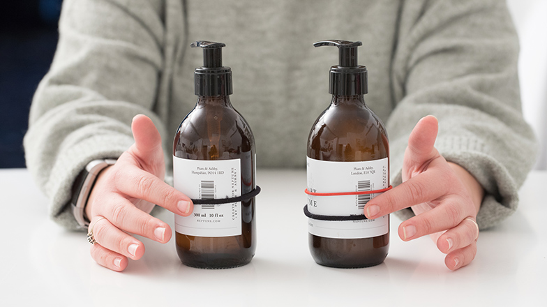 Person pointing at two bottles, one with one elastic band around it, and the other with two
