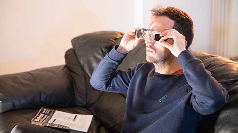 A picture of a man sitting on the sofa using TV viewing glasses
