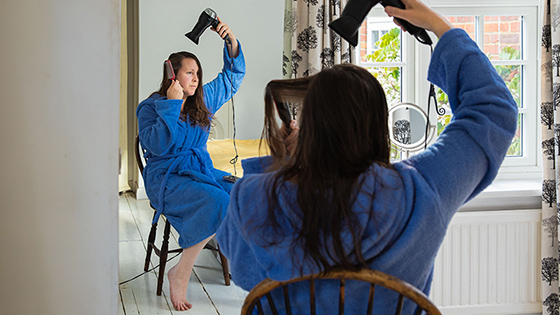 Woman blow drying her hair in front of a mirror while sitting in a chair