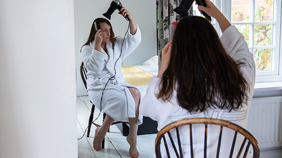 Women blow drying her hair in front of a mirror while sitting in a chair