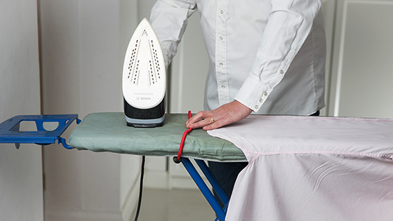 A man placing an iron on an ironing board