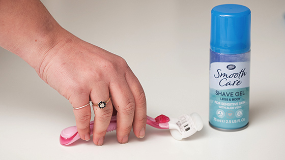 A hand picking up a razor next to shaving foam
