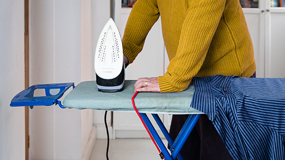 A woman placing an iron on an ironing board