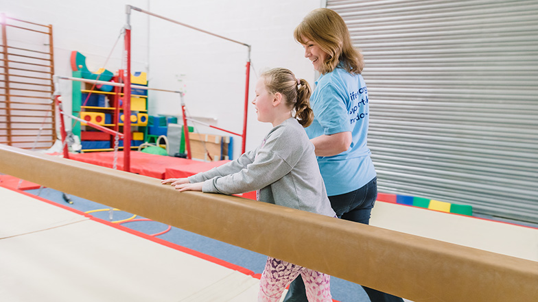 Young girl with Guide Dogs habilitation specialist in a gym