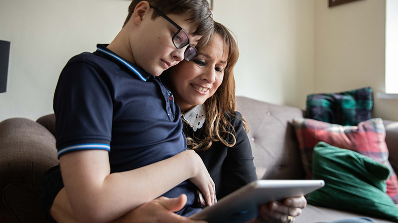 Will and his mum on the sofa looking at an iPad screen