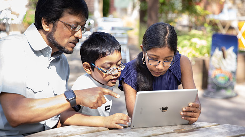 Dad with son and daughter all looking at an iPad screen at a garden table