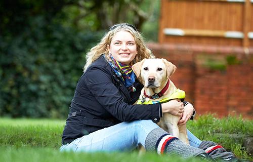 Volunteer Anica hugs her guide dog